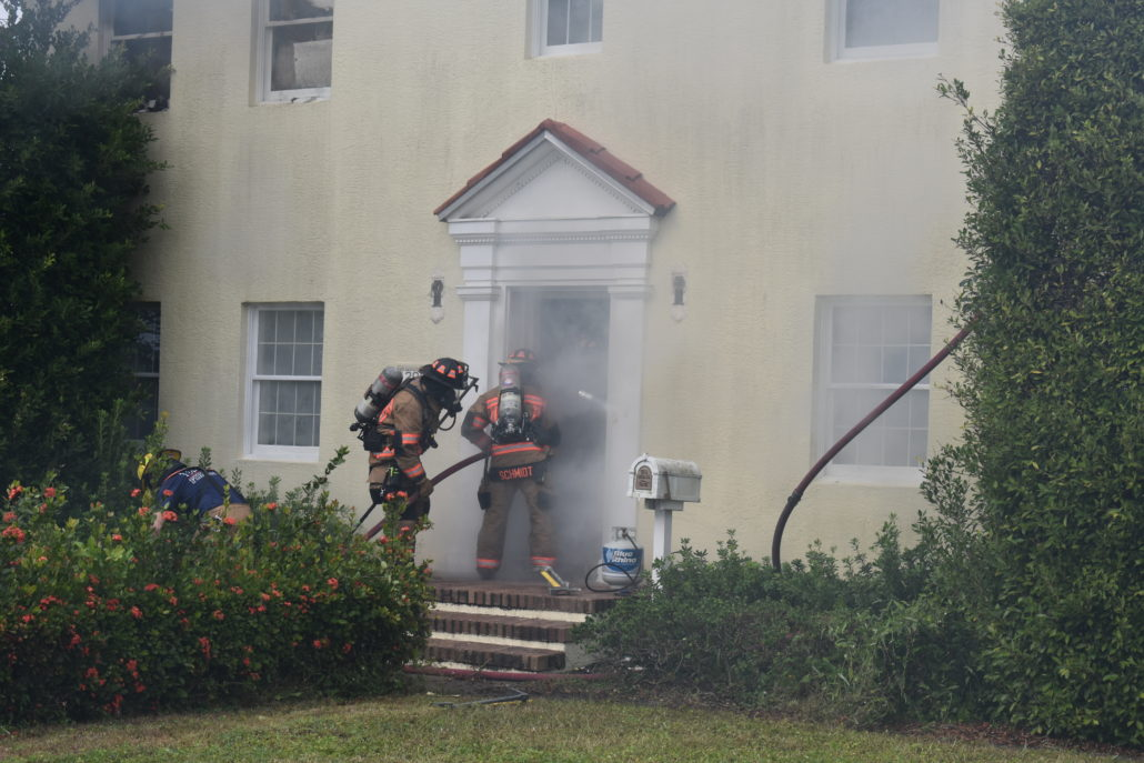 Firefighters entering a house on fire